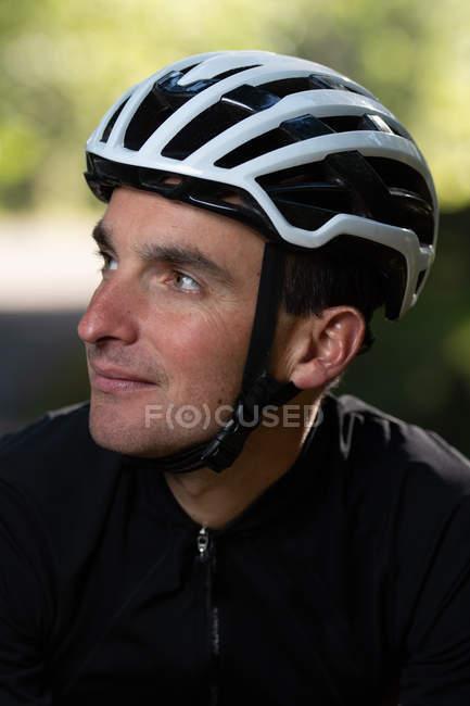 Cycliste positif regardant loin dans le parc — Photo de stock