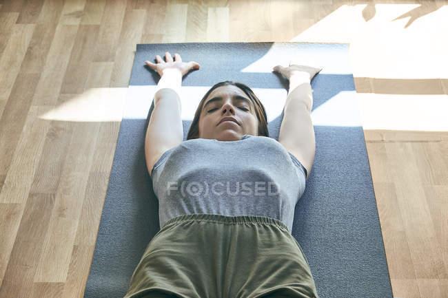 Гнучка молода жінка в спортивному лаві лежить на маті в позі відлюдника, а йога на підлозі в спортзалі. — стокове фото