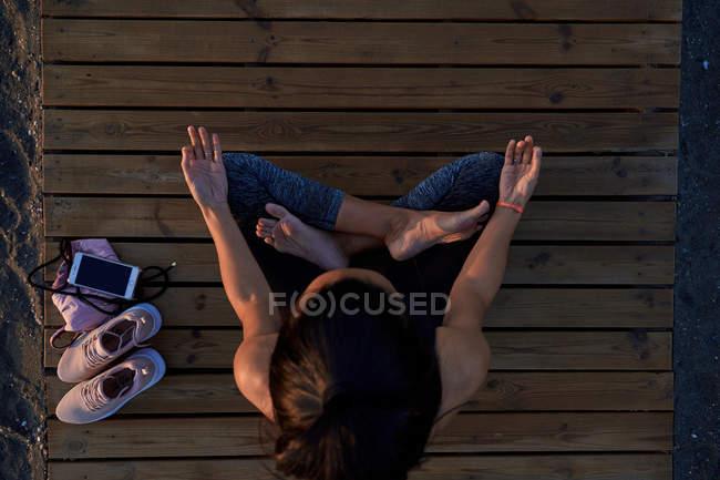 Сверху бароногая самка в костюме, сидящая в позе лотоса на дорожке и медитирующая во время занятий йогой — стоковое фото