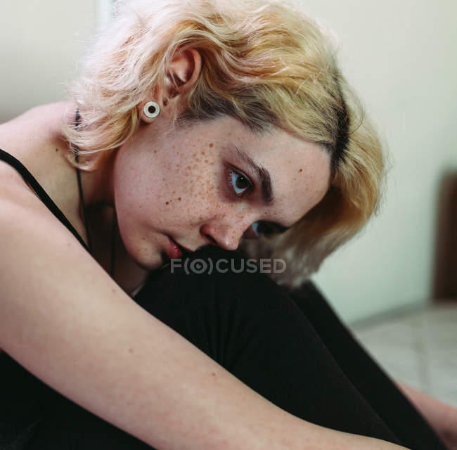 Atento pensativo jovem mulher sentada na cama e olhando para longe — Fotografia de Stock