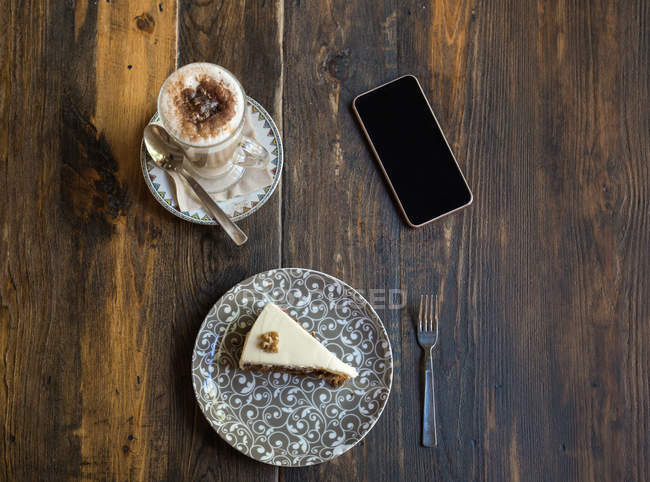 Blank screen smartphone next to coffee and cake on plate with ornament on wooden table — Stock Photo
