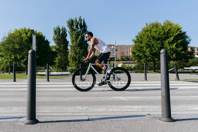 Side view of athletic man in sunglasses wearing white shirt and black shorts riding bike on city roadway with green trees on roadside on summer day with blue sky — Stock Photo