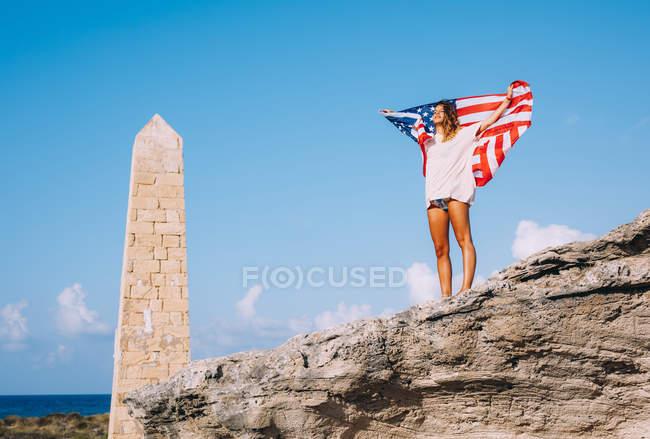 Веселая загорелая женщина в отпуске, стоящая на скалах и держа американский флаг под качающимся обелиском — стоковое фото