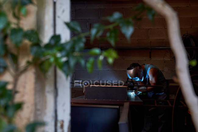 Views from tree branch leaves of professional master in protective face mask soldering metal while working in small workshop — Stock Photo