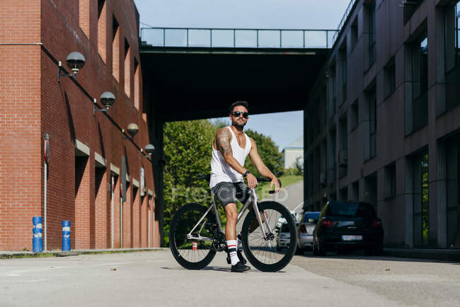 Sportive man in sunglasses wearing white sleeveless shirt and black shorts sitting on bicycle between buildings connected by bridge on summer sunny day — Stock Photo