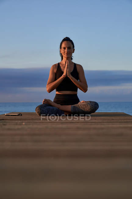 Позитивная женщина со скрещенными ногами и скрепленными руками медитирует, сидя на берегу моря под облачным вечерним небом — стоковое фото