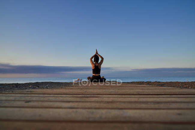 Back view female with crossed legs and meditating while sitting on seashore against cloudy evening sky — Stock Photo