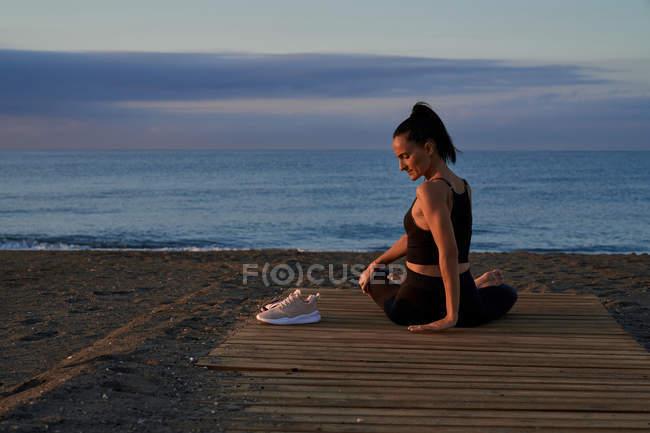 Задний вид гибкого женского скручивания тела во время сидения скрещенного ногами на берегу моря и занятия йогой вечером — стоковое фото