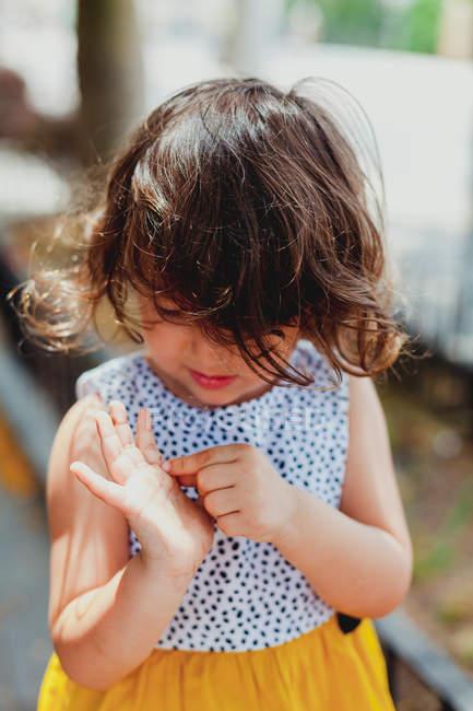 Обеспокоенный ребенок в белом и желтом платье рассматривает ладонь — стоковое фото