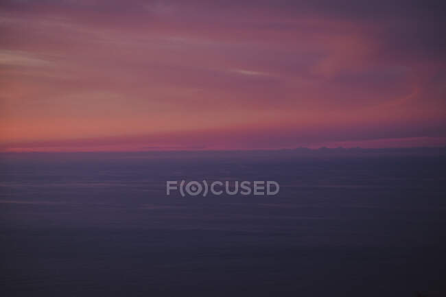 Calm gray water with smooth waves under beautiful pink and violet clouds on sky with wonderful transition during sunrise — стоковое фото