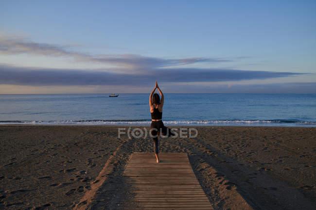 Back view female in sportswear standing in tree pose on sandy beach near waving sea in evening — Stock Photo