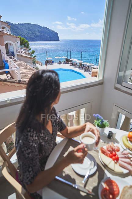 Vista lateral da mulher sorridente com penteado sentado à mesa servida tomando café da manhã com a pessoa da colheita na sala de luz em Maiorca, Espanha — Fotografia de Stock