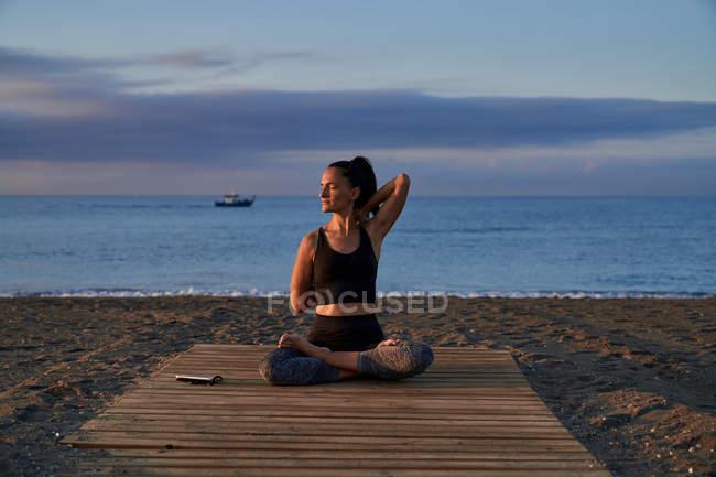 Femme positive avec jambes croisées méditant tout en étant assise sur le bord de la mer contre le ciel nuageux de la soirée — Photo de stock
