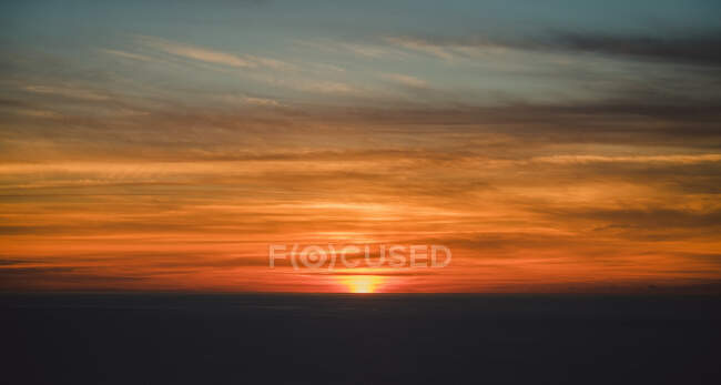 From above blurred gray horizon with hiding sun under beautiful colorful clouds on sky with wonderful transition at dusk — Stock Photo