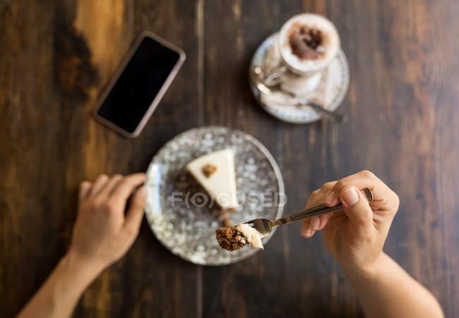 Женщина держит вилку с тортом сидит за столом с пустым экраном смартфона рядом с кофе — стоковое фото