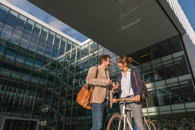 Веселые мужчина и женщина с велосипедом улыбаются и смотрят друг на друга, общаясь за пределами офисного здания — стоковое фото
