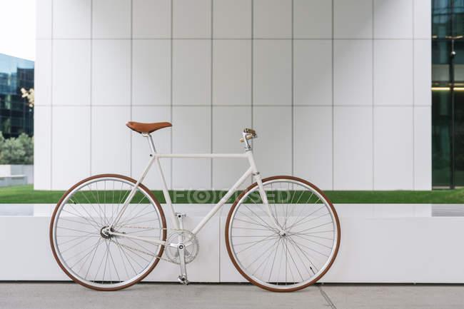 Vélo stationné sur le trottoir près du mur d'un bâtiment contemporain pendant la journée ensoleillée sur la rue de la ville — Photo de stock
