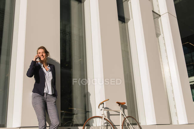 From below optimistic businesswoman on phone in jacket smiling and looking away while leaning on building wall on city street — Stock Photo