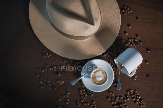 Сверху коричневый напиток с белой пеной в керамической чашке среди кофейных зерен возле шляпы и пустой кружки на деревянном столе — стоковое фото
