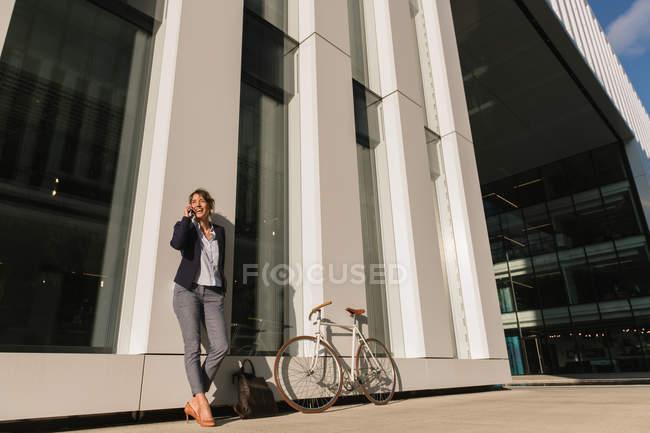 Снизу оптимистичная деловая женщина по телефону в куртке улыбается и смотрит в сторону, опираясь на стену здания на городской улице — стоковое фото