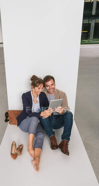 Cheerful couple embracing each other while browsing on a tablet sitting outside contemporary building on city street together — Stock Photo