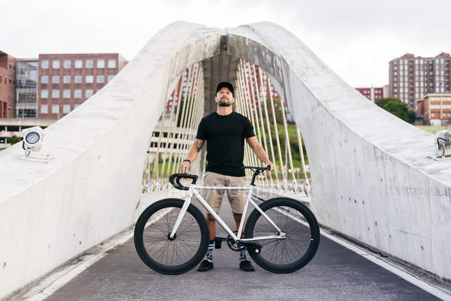 Happy adult bearded man in black cap wearing black shirt and beige shorts standing with bike across footbridge in city looking up — Stock Photo
