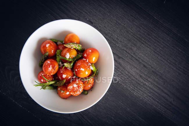Зверху смачні вишневі помідори з зеленою спаржею та розмариною на білій тарілці сірого кольору. — стокове фото
