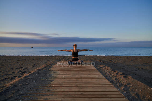 Slim woman in sportswear sitting on sandy beach with outstretched arms near waving sea in evening — Stock Photo