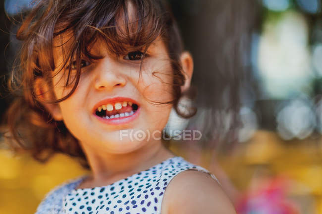 Curly adorable girl looking at camera with wide smile showing teeth in park — Stock Photo