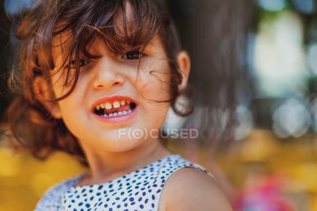 Кудрявая обожаемая девушка смотрит на камеру с широкой улыбкой, показывая зубы в парке — стоковое фото