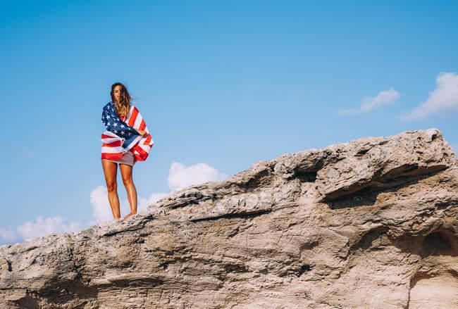 Веселая женщина, завернутая в американский флаг, стоящая на скалистых скалах в голубом небе — стоковое фото