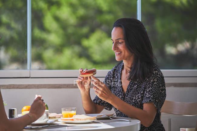 Вид сбоку улыбающейся голодной женщины с прической, сидящей за подаваемым столом и поедающей сэндвич в Осаке, Испания — стоковое фото