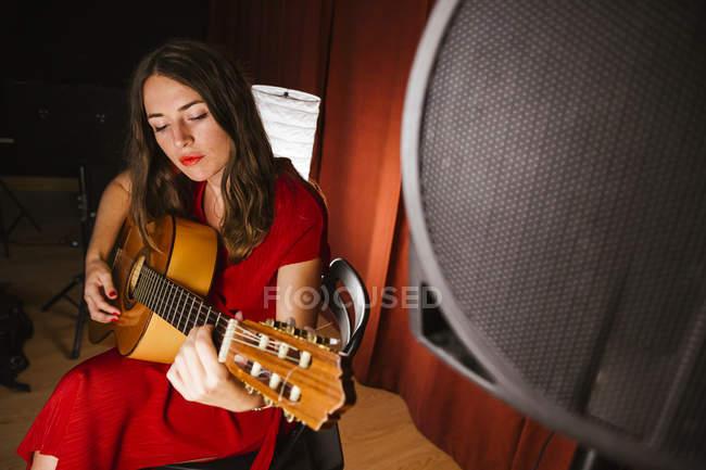 Charmante künstlerische Frau im roten Kleid, die bei warmem Licht auf der Bühne ein Lied auf der Gitarre spielt — Stockfoto