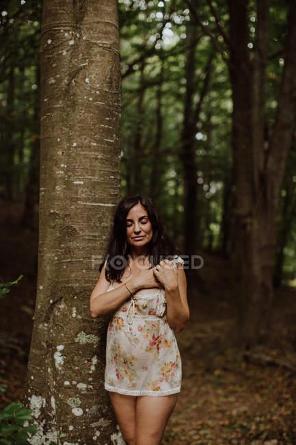 Застенчивая чувственная женщина, стоящая на камне в лесу — стоковое фото
