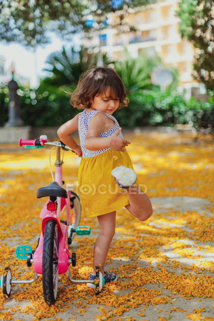 Girl riding on bicycle and looking down in park — Stock Photo