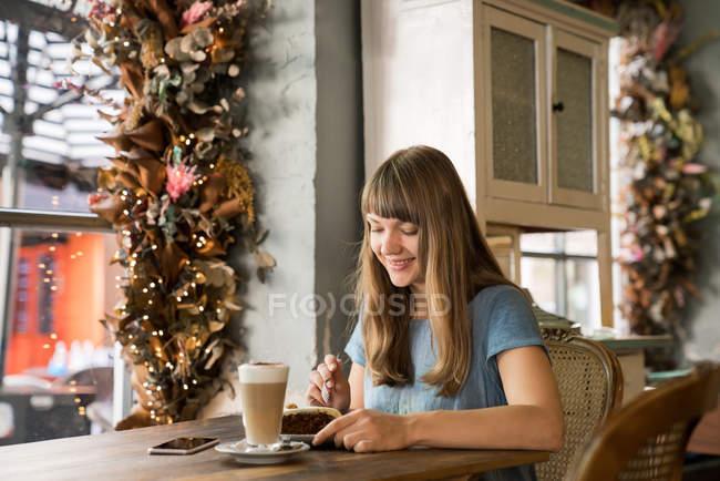 Блондинка счастливая молодая женщина с челкой улыбается и ест десерт в уютном кафе — стоковое фото