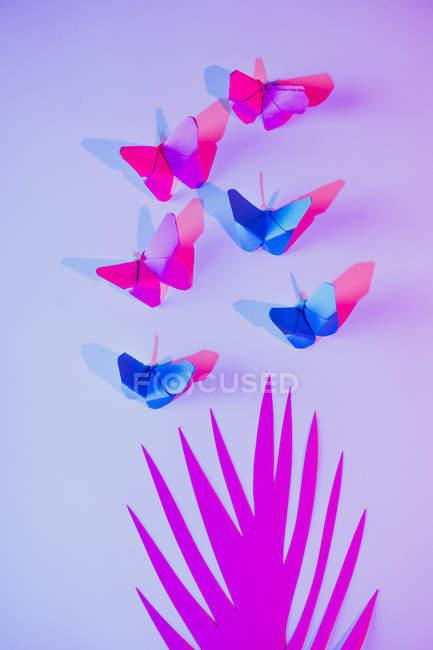 Farfalle rosa e blu attaccate alla parete lilla su foglia di carta intagliata — Foto stock