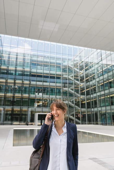 Heureuse femme d'affaires au téléphone en veste souriant et regardant loin tout en s'appuyant sur le mur de construction sur la rue de la ville — Photo de stock