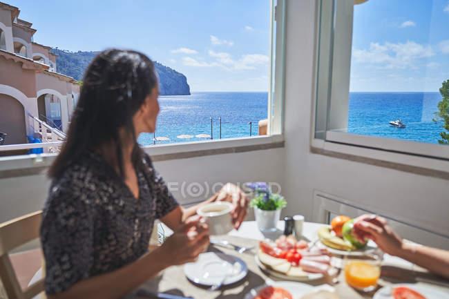 Vista lateral de una mujer sonriente con peinado sentada en la mesa servida desayunando con una persona de la cosecha en la sala de luz en Mallorca, España - foto de stock