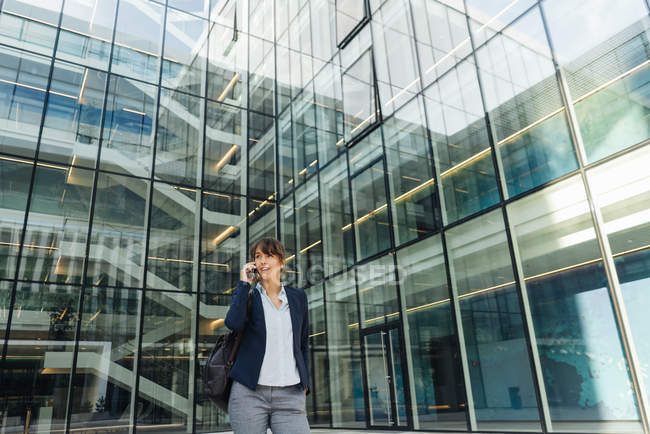 Low angle of happy businesswoman talking on smartphone while standing outside business center on city street — Stock Photo