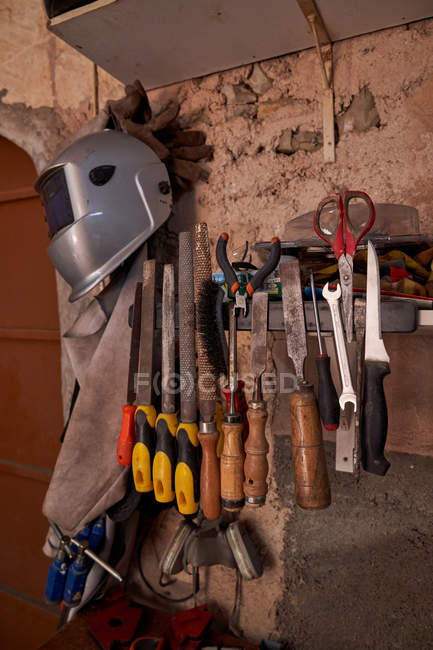 Set of work tools and protective clothes for welding and soldering hanging on old flake wall of workshop — Stock Photo