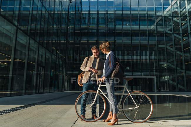 Homme et femme joyeux avec vélo souriant et se regardant tout en communiquant à l'extérieur de l'immeuble de bureaux — Photo de stock