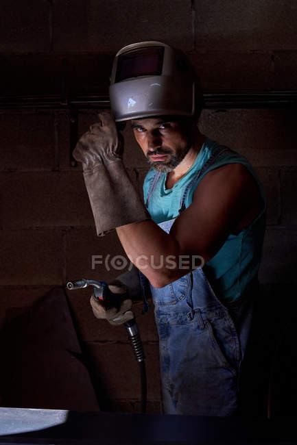 Професійний чоловік із зварювальною маскою на голові, одягнений у джинси, що стоять на робочому місці, і захисні рукавички. — Stock Photo