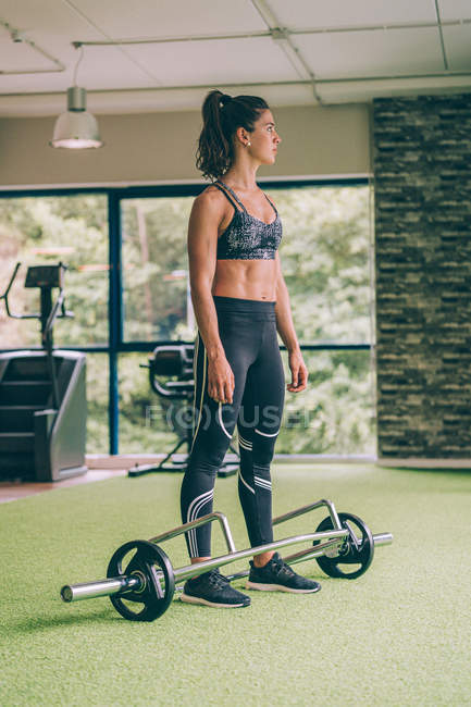 Muscular woman in sportswear lifting heavy barbell and looking away during workout in gym — Stock Photo
