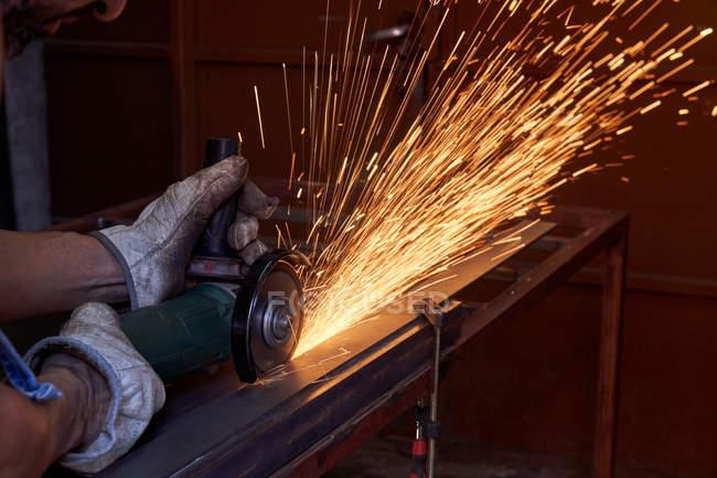 Geschnittenes Bild eines Arbeiters mit Schutzbrille und Handschuhen, der während der Arbeit in der Werkstatt mit einem Schleifer mit Funkenflug Metall schneidet — Stockfoto