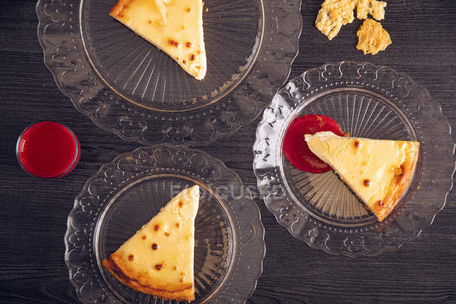 From above tasty cheesecake pieces with appetizing raspberry jam in ornamental glass plates — Stock Photo
