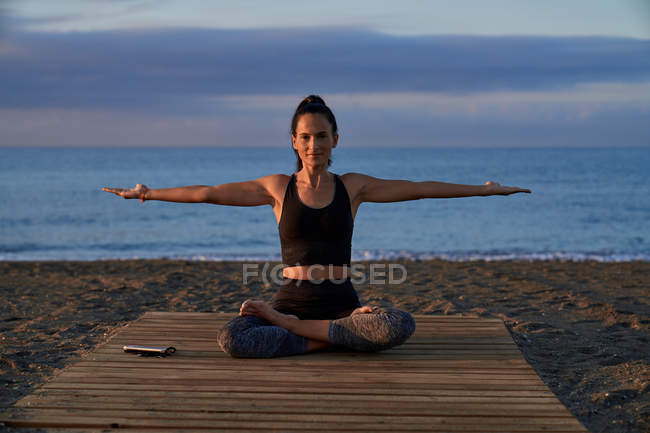 Positive woman with crossed legs meditating while sitting on seashore against cloudy evening sky — Stock Photo