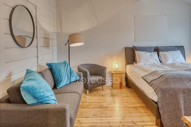 Chambre confortable avec murs en bois blanc et grand lit doux avec canapé gris confortable près du lampadaire en feu — Photo de stock