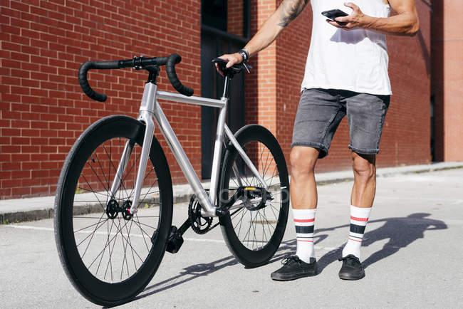 Imagem cortada de ciclista em sportswear usando smartphone enquanto de pé com bicicleta ao lado da parede de tijolo vermelho — Fotografia de Stock