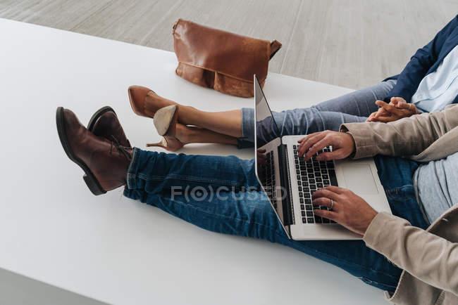 Обрезанные изображения бизнесменов, просматривающих ноутбук вместе, сидя снаружи современного здания на городской улице — стоковое фото